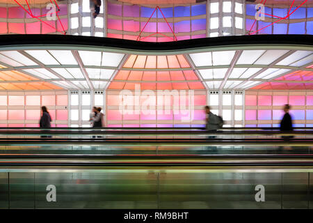 Air passengers people walking colourful neon lights art installation, Michael Hayden, pedestrian tunnel Chicago O'Hare International Airport Terminal. - Stock Image