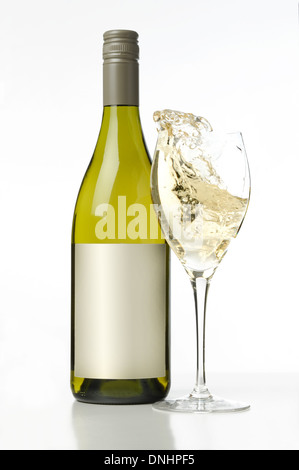 A bottle of white wine with a splashing glass of white wine. - Stock Image