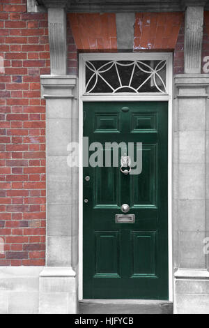 Grand antique green wooden door part of a home - Stock Image