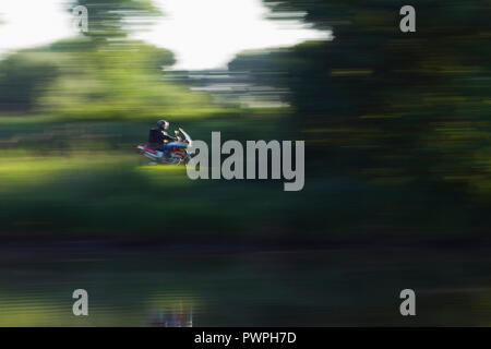 France, motorcyclist following the Canal de La Martiniere, spring. - Stock Image