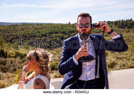 Newlyweds pose in the middle of nature with vintage phones - Stock Image