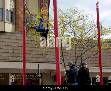 Two Rivers, Wisconsin USA, 13th Oct, 2018.  Young girl does a flip on a controlled bungee rebounder trampoline during street fair at Two Rivers Annual Autumn Applefest. Credit: Jerome Wilson/Alamy Live News - Stock Image