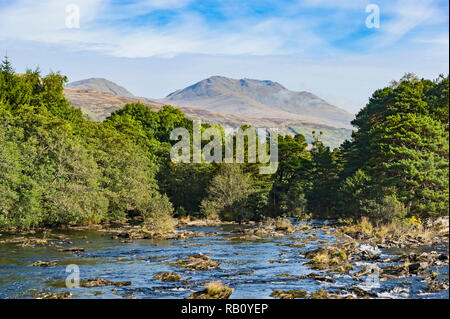 The Falls of Dochart at Killin in Scotland on a sunny autumn day with Ben Lawers (R) and Beinn Ghlas (L) providing the backdrop - Stock Image