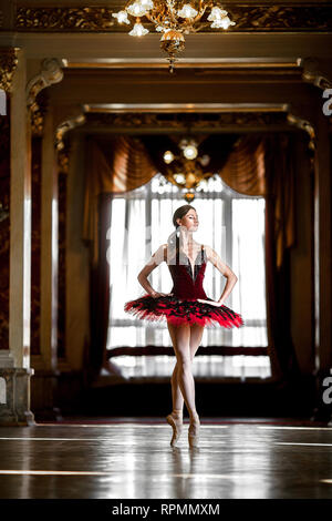 Beautiful ballerina dancing in a luxurious hall with a chandelier in a red dress against the window. - Stock Image