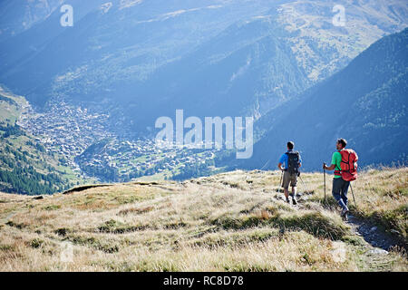 Hikers on grassy cliff overlooking valley, Mont Cervin, Matterhorn, Valais, Switzerland - Stock Image