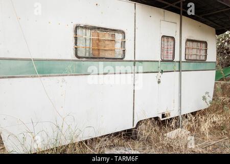 Old caravan in overgrown field. - Stock Image