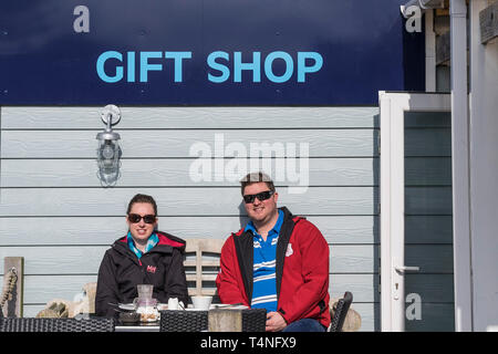 Customers wearing sunglasses relaxing in the Spring sunshine outside a small gift shop in Newquay in Cornwall. - Stock Image