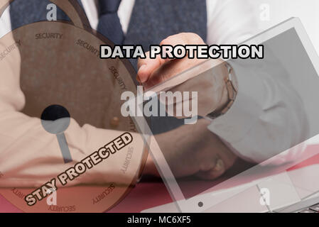 Business man sittig behind desk pushing virtual screen with the words data protection and stay stay protected. - Stock Image