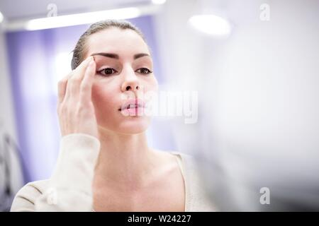 Woman looking in mirror in clinic. - Stock Image