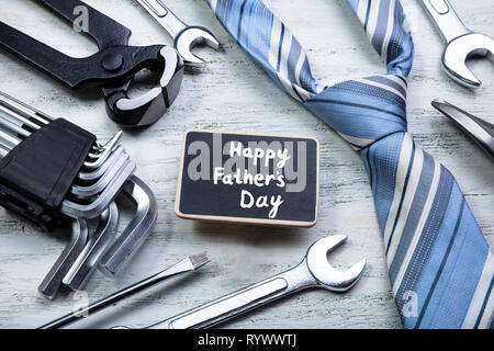 Slate With Happy Father's Day Text Surrounded With Work Tools And Tie On Wooden Table - Stock Image