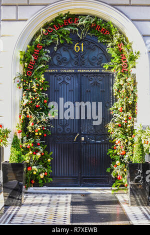 Queen's College Preparatory School entrance door with Christmas decorations. Queen Elizabeth the Queen Mother opened the College in Portland Place - Stock Image