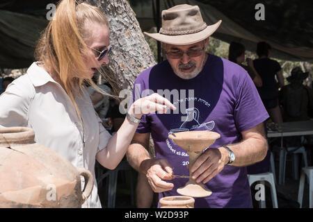 Kiryat Gat, Israel. 8th July, 2019. Archaeologists Prof. Yosef Garfinkel (R) and Dr. Katia Cytryn-Silverman (L) of the Hebrew University inspect artifacts discovered at the site of Khirbet a Rai in the Judaean foothills, between Kiryat Gat and Lachish. Credit: Nir Alon/Alamy Live News Credit: Nir Alon/Alamy Live News Credit: Nir Alon/Alamy Live News - Stock Image