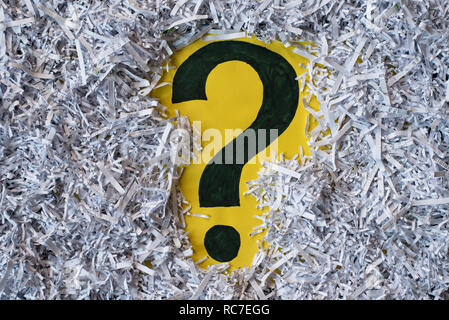 Question mark symbol in a shredded paper. Concept of confidential office paperwork, faq and questions - Stock Image