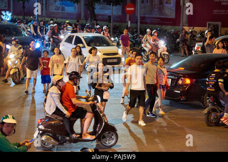 Night shot of pedestrians crossing road full of mopeds in busy street in Hanoi, Vietnam. The seemingly chaotic traffic scares tourists but is commonpl - Stock Image