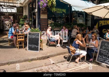 People sitting outside enjoying sunny weather and coffee, Boyces Ave, Bristol, UK - Stock Image