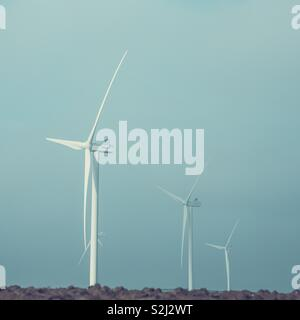 Minimalist wind farm windmills with a colourful background and copy space - Stock Image