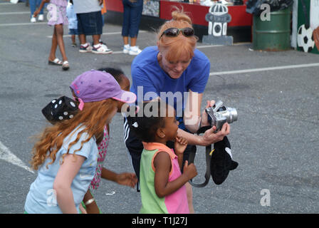 woman show little children their picture on a digitital camera - Stock Image
