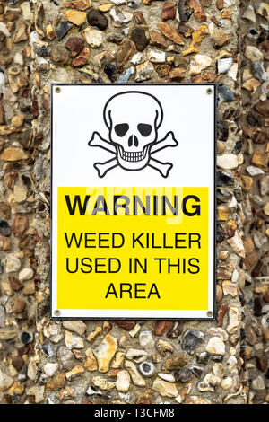 Weed killer usage warning sign attached to pebble dashed wall - Stock Image