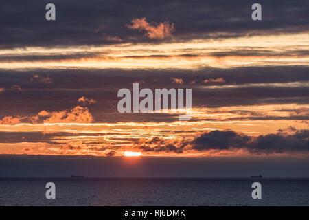 zwei Schiffe am Horizont mit untergehender Sonne - Stock Image