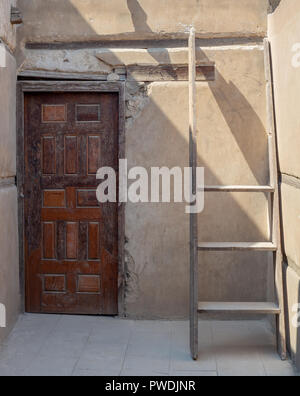 Stone wall with wooden grunge old decorated door and broken wooden ladder, Cairo, Egypt - Stock Image