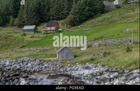 Rural Norwegian landscape with a house and two barns. - Stock Image