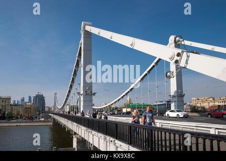 People and cars crossing Krymsky Bridge (Crimean Bridge) over the Moskva river, looking west towards Frunzenskaya - Stock Image