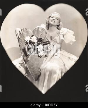 Woman holding a heart-shaped box - Stock Image