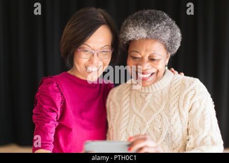 Smiling active senior women taking selfie with camera phone - Stock Image