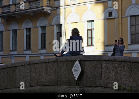 Woman posing for mobile phone photo on bridge balustrade - Stock Image