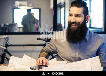 Architect smiling in office - Stock Image