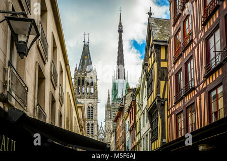 The main street Rue du Gros Horloge with the Rouen Cathedral tower and spires in view and half timbered homes along - Stock Image