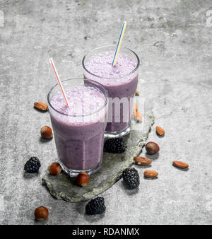 BlackBerry smoothie with nuts. On rustic background. - Stock Image