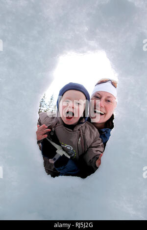 Mother and sun playing in the snow - Stock Image
