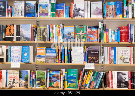 Cambridge, England - October 2018: Interior of a modern Waterstones bookshop with wooden shelves full of books. Section of travel books and guides. - Stock Image