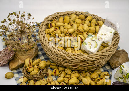 Stones and dried flowers next to fried pistachios, persimmons and nougat in a wicker basket and a white plate on paper of blue squares - Stock Image