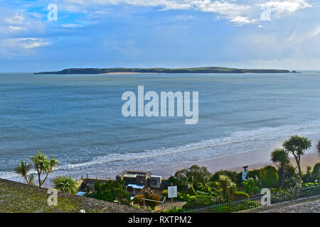 The view across the water from The Esplanade in the resort of Tenby, towards Caldey Island, home to Cistercian monks who still occupy Caldey Abbey. - Stock Image