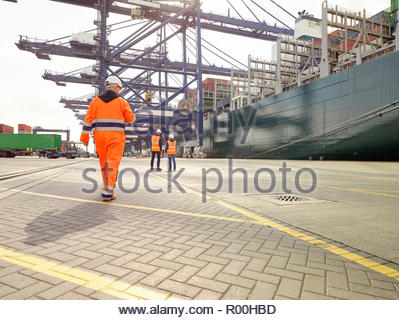 Dock workers beside cargo ship at Port of Felixstowe, England - Stock Image