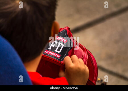 Los Angeles, California, USA 12 May 2018 A Young Firefighter watching Los Angeles City Firefighters from Station 27 doing a demo of a car rescue on Fire Service Day. Credit: Chester Brown/Alamy Live News. - Stock Image