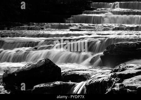 The raw power of water cascading over limestone steps at Lower Force, Aysgarth, Wensleydale, Yorkshire. UK - Stock Image