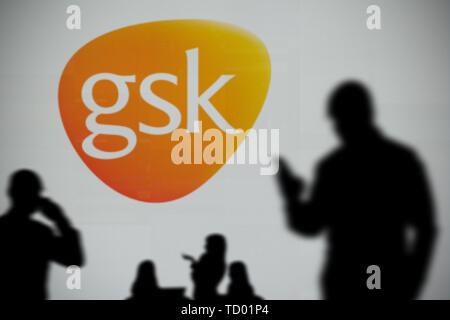 The GSK logo is seen on an LED screen in the background while a silhouetted person uses a smartphone in the foreground (Editorial use only) - Stock Image