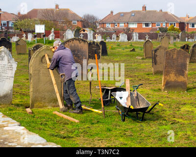 A stonemason at work re-erecting a fallen gravestone in the cemetery at St Germains Churcyard Marske by the Sea  North Yorkshire England UK - Stock Image