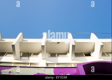 Part of a weathered concrete building with a blue sky - Stock Image