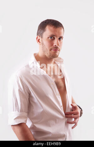 Young elegant man with beautiful face, muscular torso, dressed in white unbuttoned shirt - Stock Image