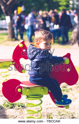 Young boy sitting on a red horse shaped spring - Stock Image