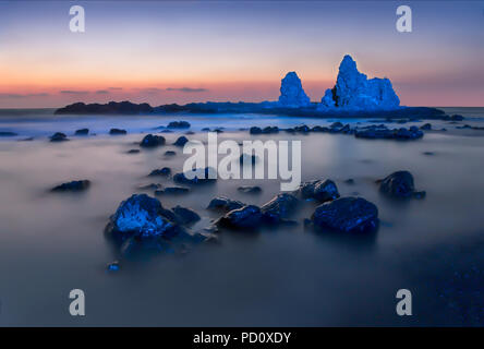 Long exposure photograph of waves lapping rocks lit with a blue light in rough seas in Cyprus - Stock Image