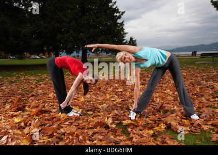 Two young women stretching their muscles at Spanish Bank in Vancouver, British Columbia, Canada - Stock Image