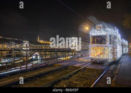 Budapest, Hungary - Festively decorated light tram (fenyvillamos) on the move with Szechenyi Chain Bridge, Matthias Church and Fisherman's Bastion by  - Stock Image