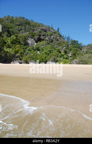 Sea lapping the shoreline, sandy beach with granite rocks and hoop pines behind, Radical bay, Magnetic Island, Queensland, Australia - Stock Image