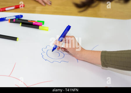 Student hand with blue felt pen drawing simple stickman on big white paper on desk in classroom. Colorful pens spilled on paper. Education concept - Stock Image