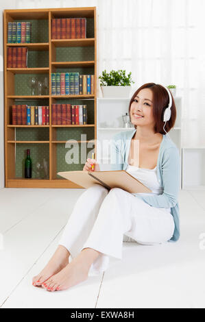 Young woman sitting on the floor and holding a pencil with smile, - Stock Image